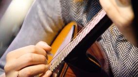 Guitarra acústica hermosa del primer que es jugada por la mujer que se sienta, concepto del músico Mujer que juega el primer de l Fotografía de archivo libre de regalías