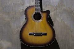Guitarra acústica no fundo da parede imagens de stock royalty free