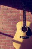 Guitarra acústica que inclina-se na parede de tijolo vermelho Fotografia de Stock Royalty Free