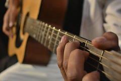 Guitarra acústica que juega acordes fotos de archivo