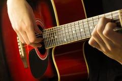 A guitarra acústica vermelha, fundo escuro, senta o músico que joga no jogo espanhol, musical clássico da escola para crianças Imagem de Stock Royalty Free