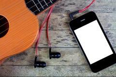 Guitarra, auriculares y teléfono elegante Fotografía de archivo libre de regalías