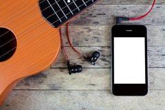 Guitarra, auriculares y teléfono elegante Foto de archivo