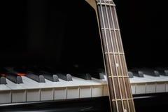 Guitarra baja contra llaves del piano de cola Fotos de archivo libres de regalías