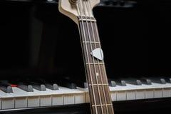 Guitarra baja contra llaves del piano de cola Imagenes de archivo