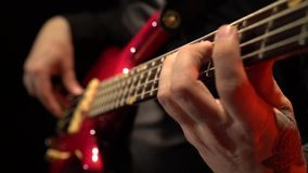 Guitarra baja Digitación de los fingeres las secuencias Cierre para arriba Fondo negro almacen de video