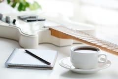 Guitarra, café, libreta y lápiz imagen de archivo