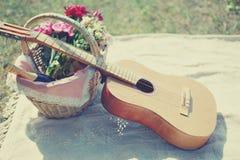 Guitarra, cesta con el vino y ramo de flores Imagen de archivo libre de regalías