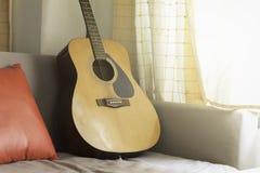Guitarra clásica con la almohada roja en el sofá Fotografía de archivo libre de regalías