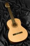Guitarra clásica en fondo de seda negro Fotos de archivo libres de regalías