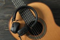 Guitarra clássica bonita com os fones de ouvido no fundo de madeira foto de stock