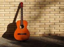 Guitarra clássica em um passeio e descanso em uma parede de tijolo amarela Fotografia de Stock Royalty Free