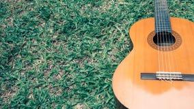 Guitarra clássica na obscuridade - grama verde com espaço da cópia imagem de stock