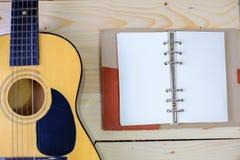 Guitarra com um caderno no assoalho de madeira foto de stock