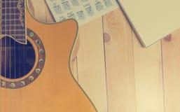 Guitarra con el cuaderno en blanco para la escritura de la canción Imagenes de archivo
