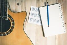 Guitarra con el cuaderno en blanco para la escritura de la canción Fotos de archivo