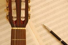 Guitarra con la pluma en el manuscrito de la música Fotografía de archivo