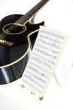 Guitarra con música escrita en un soporte Imagenes de archivo