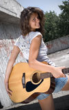 Guitarra da terra arrendada da menina e vista da câmera Foto de Stock