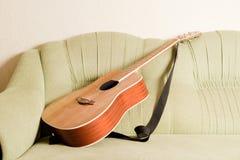 Guitarra de Akustic no sofá Imagens de Stock