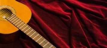 Guitarra de nylon clássica que encontra-se na matéria têxtil vermelha de veludo, apresentação artística do instrumento Foto de Stock