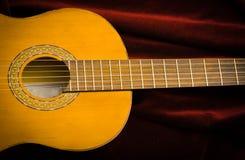 Guitarra de nylon clássica que encontra-se na matéria têxtil vermelha de veludo, apresentação artística do instrumento Imagens de Stock