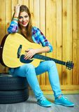 Guitarra del control de la muchacha, sentándose en las ruedas de un coche Imagen de archivo libre de regalías