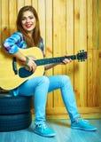 Guitarra del control de la muchacha, sentándose en las ruedas de un coche Fotografía de archivo libre de regalías