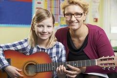 Guitarra del juego de Helping Pupil To del profesor en la lección de música Imagenes de archivo