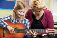 Guitarra del juego de Helping Pupil To del profesor en la lección de música imagen de archivo