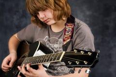 Guitarra del juego del muchacho imagenes de archivo
