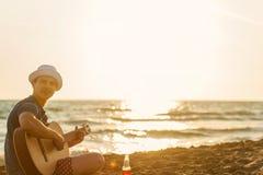 Guitarra del juego del hombre joven en la playa y gozar en puesta del sol foto de archivo libre de regalías