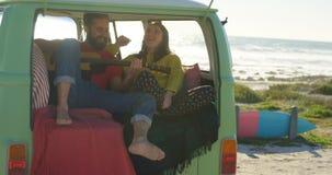 Guitarra del juego del hombre para la mujer en la furgoneta 4k metrajes