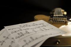 Guitarra do archtop do vintage na opinião de ângulo alto natural do close-up do bordo com as folhas de música no fundo preto foto de stock