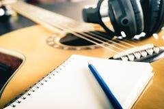Guitarra e fones de ouvido com caderno vazio fotografia de stock