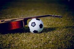 A guitarra e o futebol são colocados em gramados verdes Música e esportes fotos de stock royalty free