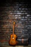 Guitarra e saco retro no fundo da parede de tijolo Fotos de Stock Royalty Free
