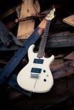Guitarra eléctrica blanca en un woodpile Fotografía de archivo