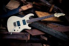 Guitarra eléctrica blanca en un woodpile Fotos de archivo