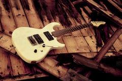 Guitarra eléctrica blanca en un woodpile Fotos de archivo libres de regalías