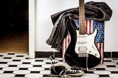 Guitarra eléctrica, chaqueta de cuero y zapatos de los deportes imagenes de archivo