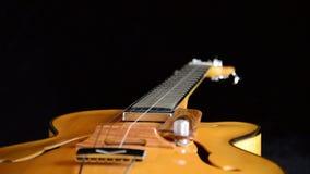 Guitarra eléctrica clásica del jazz que gira en el fondo negro metrajes