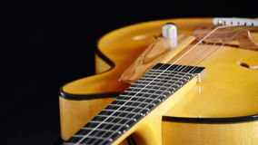 Guitarra eléctrica clásica del jazz que gira en el fondo negro almacen de video