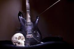 Guitarra eléctrica con el cráneo que se coloca cerca de la pared Foto de archivo