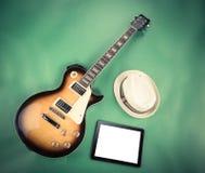 Guitarra eléctrica con la libreta y cámara vieja en fondo verde Fotos de archivo