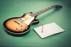 Guitarra eléctrica con la libreta y cámara vieja en fondo verde Imagenes de archivo
