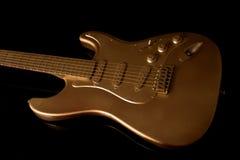 Guitarra eléctrica del oro en un fondo oscuro Imagen de archivo libre de regalías