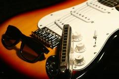 Guitarra eléctrica del vintage, armónica, gafas de sol en fondo negro Fotos de archivo