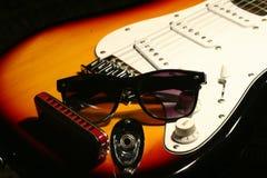 Guitarra eléctrica del vintage, armónica, gafas de sol en fondo negro Imagen de archivo libre de regalías