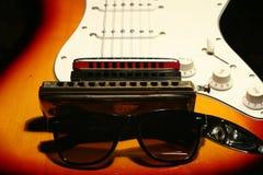 Guitarra eléctrica del vintage, armónica, gafas de sol en fondo negro imagen de archivo